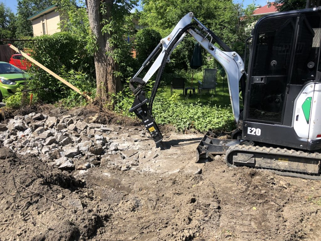 Our bobcat e20 equipped with a demolition hammer breaking up an old concrete slab in Ottawa